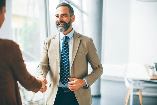 Älteres geschäftsmannhändeschütteln mit junger frau im büro