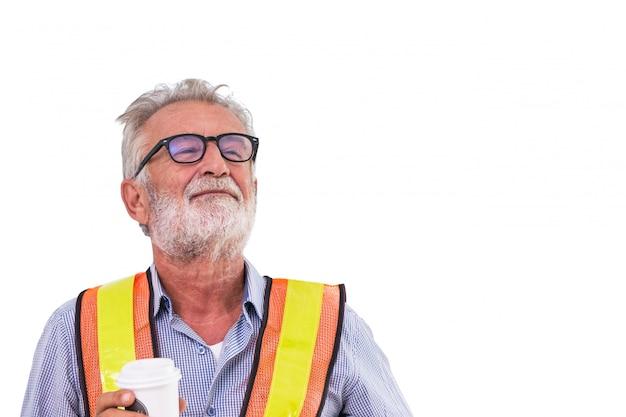 Älteres ingenieurarbeitskraftlächeln des alten mannes und halten der kaffeetasse lokalisiert auf weißem hintergrund