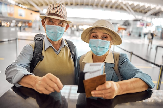 Älteres kaukasisches paar mit ausländischen pässen und bordkarten, die am check-in-schalter des flughafens stehen