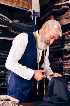 Älteres männliches schneiderausschnittstück stoff bei tisch in seinem shop