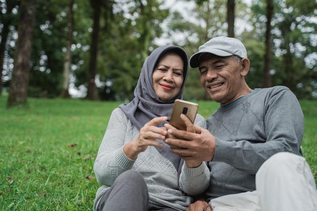 Älteres muslimisches paar, das smartphone zusammen im park verwendet