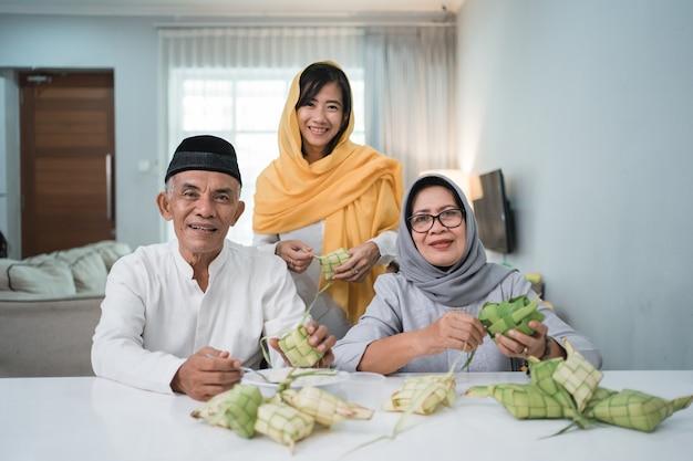 Älteres muslimisches paar und tochter, die ketupat für eid fitr mubarak feier zu hause machen