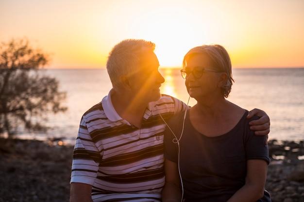 Älteres paar am strand bei sonnenuntergang - rentnerehepaar hört zusammen mit den gleichen kopfhörern musik
