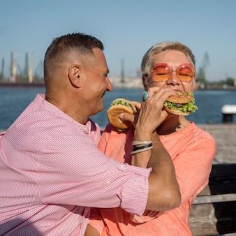 Älteres paar am strand, das burger isst
