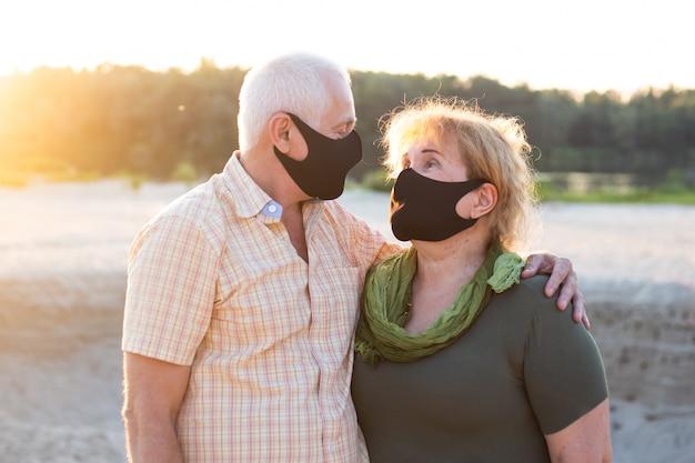 Älteres paar am strand, das medizinische maske trägt, um am sommertag vor coronavirus zu schützen, coronavirus-quarantäne
