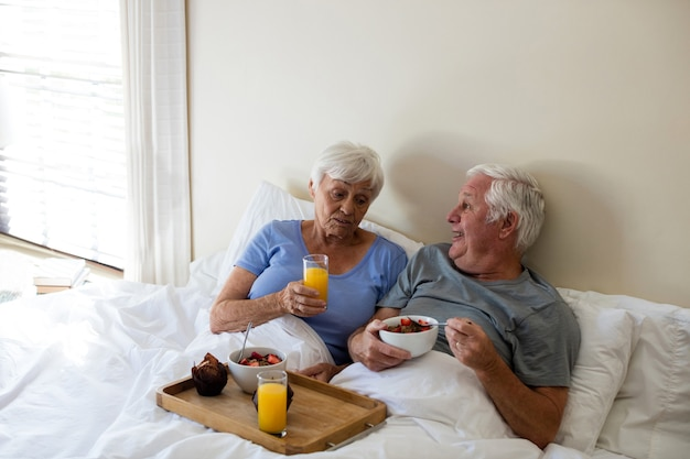 Älteres paar beim frühstück im schlafzimmer zu hause
