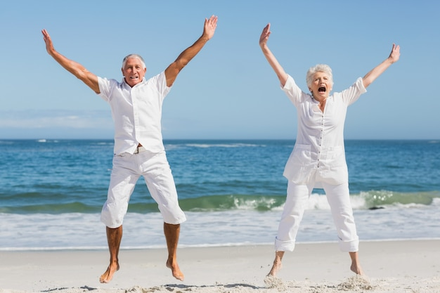 Älteres paar, das am strand springt