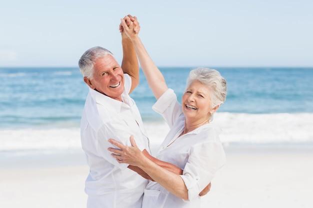 Älteres paar, das am strand tanzt