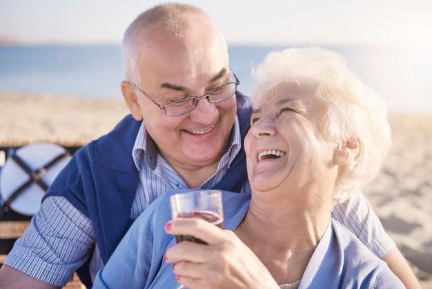 Älteres paar, das am strand umarmt und rotwein trinkt