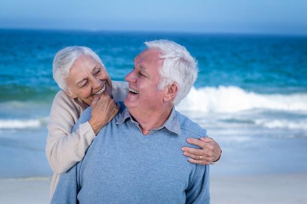 Älteres paar, das am strand umarmt