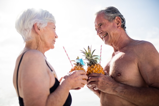 Älteres paar, das ananas-cocktail am strand hat