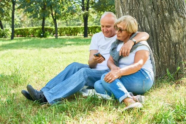 Älteres paar, das auf dem gras sitzt