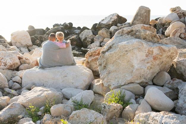 Älteres paar, das auf felsenrückansicht sitzt