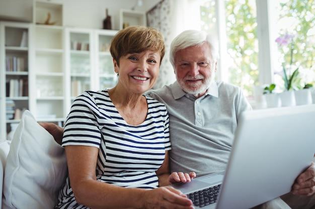 Älteres paar, das auf sofa mit einem laptop sitzt
