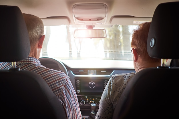 Älteres paar, das auto während der straßenfahrt fährt. blick von hinten.