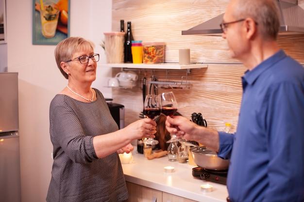 Älteres paar, das beziehungsjubiläum mit rotwein feiert. altes verliebtes paar, das während des gesunden essens ein angenehmes gespräch führt.
