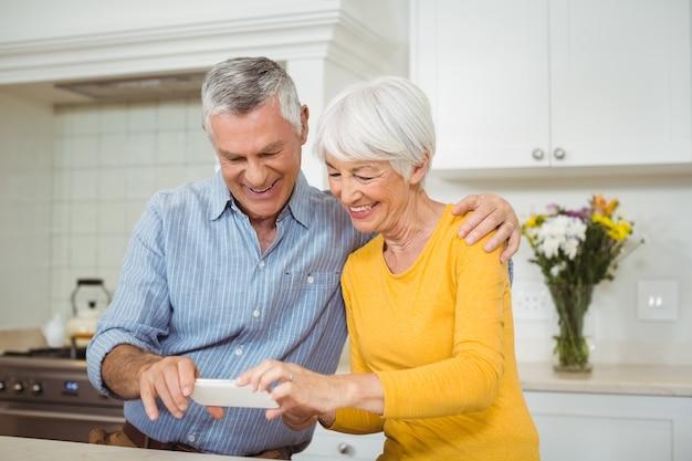 Älteres paar, das bilder auf handy in der küche betrachtet