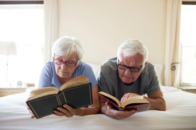 Älteres paar, das bücher auf bett im schlafzimmer liest