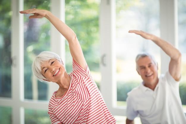 Älteres paar, das dehnungsübung zu hause durchführt