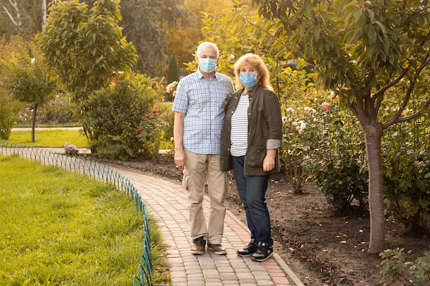 Älteres paar, das draußen medizinische masken trägt