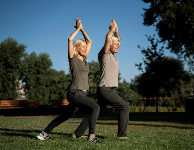 Älteres paar, das draußen yoga macht