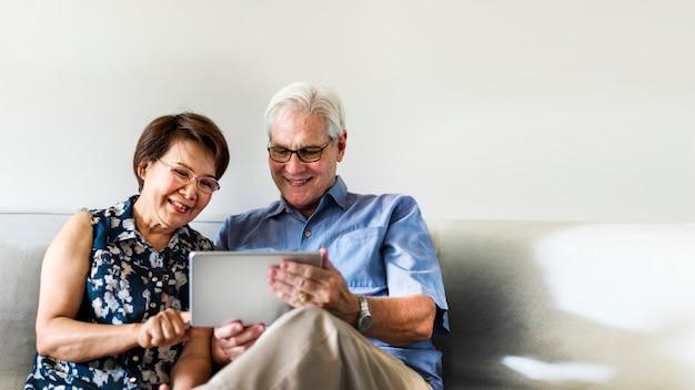 Älteres paar, das ein digitales gerät in einem wohnzimmer verwendet
