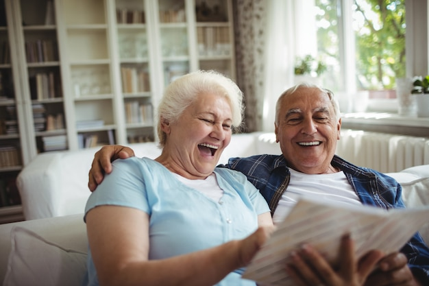 Älteres paar, das ein fotoalbum betrachtet