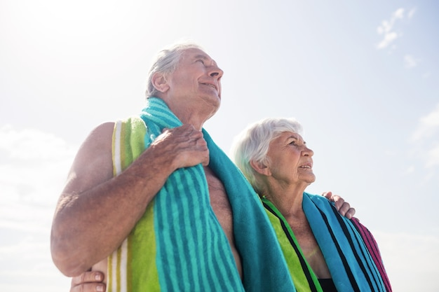 Älteres paar, das ein handtuch um den hals hält