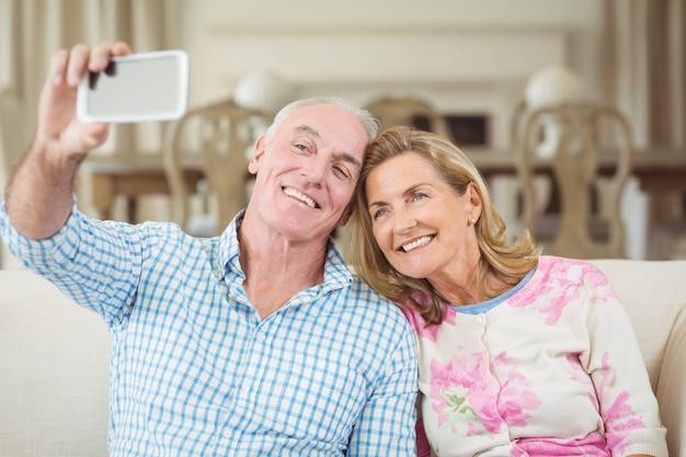 Älteres paar, das ein selfie auf handy im wohnzimmer nimmt
