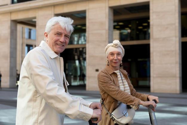 Älteres paar, das einen elektroroller in der stadt fährt