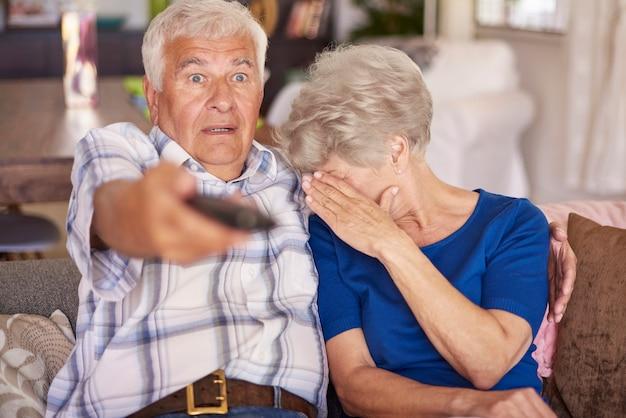 Älteres paar, das einen horrorfilm im fernsehen sieht