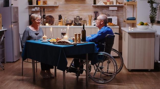 Älteres paar, das für ein romantisches abendessen nach hause kommt. alter mann im rollstuhl, der mit seiner fröhlichen frau am tisch in der küche sitzt. imobilisierter gelähmter behinderter ehemann beim romantischen abendessen