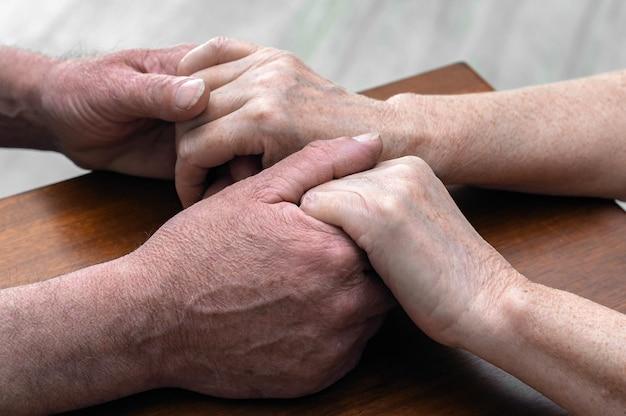 Älteres paar, das hände nah oben hält