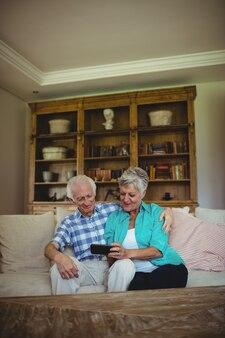 Älteres paar, das handy im wohnzimmer benutzt