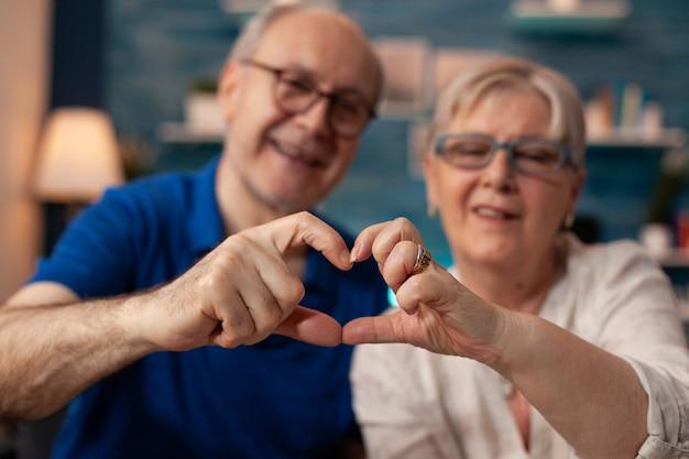 Älteres paar, das herzformfigur mit den händen herstellt