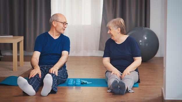 Älteres paar, das ihre körper auf yogamatte im wohnzimmer ausdehnt. gesunder lebensstil für alte menschen zu hause, training und training, sportliche aktivität zu hause