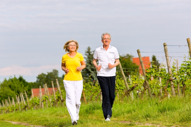 Älteres paar, das im freien sport treibt, auf einer straße oder einem weg in der natur joggt