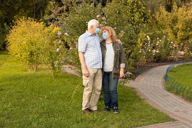 Älteres paar, das im frühjahr oder sommerpark mit medizinischer maske geht