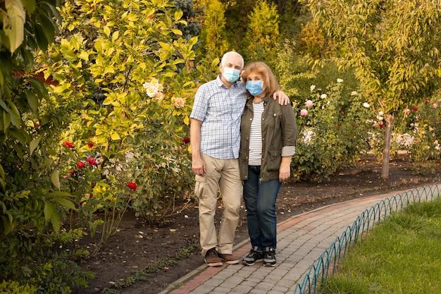 Älteres paar, das im frühlings- oder sommerpark umarmt, der medizinische maske trägt