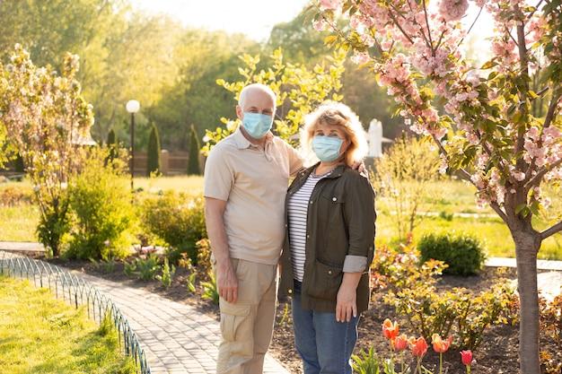 Älteres paar, das im frühlings- oder sommerpark umarmt und medizinische maske trägt, um vor coronavirus zu schützen