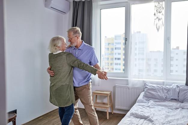Älteres paar, das im wohnzimmer tanzt, ehemann, der hand der reifen frau hält, die spaß zusammen genießt, ferien verbringt, freizeitruhe ifestyle zu hause. in lässiger haushaltskleidung