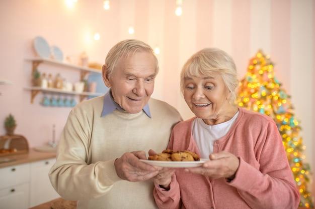 Älteres paar, das in der küche mit einem teller mit gebäck steht