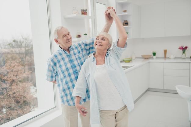 Älteres paar, das in der küche tanzt