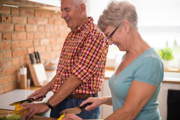 Älteres paar, das in der küche zusammenarbeitet