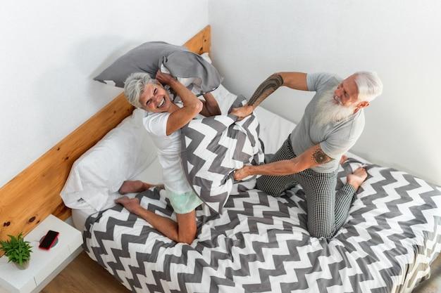 Älteres paar, das kissenschlacht während der morgenzeit zu hause tut