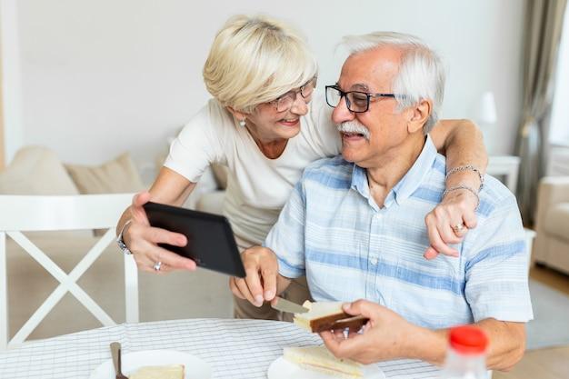 Älteres paar, das lächelt und dieselbe tafel betrachtet. altes paar, das videoanruf mit freunden oder familie hat