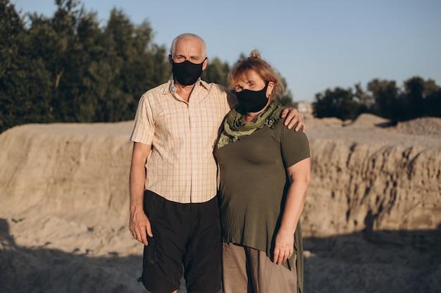 Älteres paar, das medizinische maske trägt, um vor coronavirus draußen in der sommernatur zu schützen, coronavirus-quarantäne