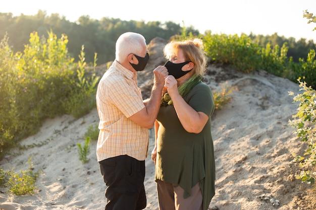 Älteres paar, das medizinische masken trägt, um am sommertag vor coronavirus zu schützen