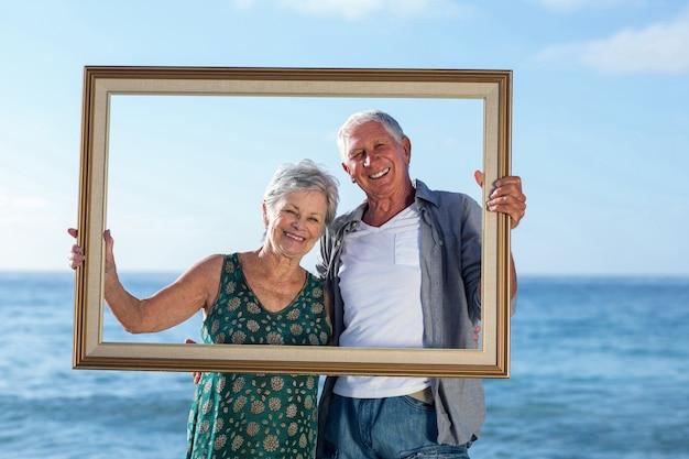Älteres paar, das mit einem rahmen aufwirft