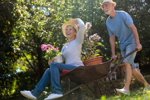Älteres paar, das mit einer schubkarre spielt